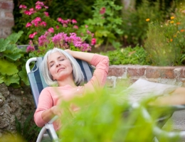 F57, Woman sitting in lawn chair in her garden, Memmingen, Bavaria, Germany